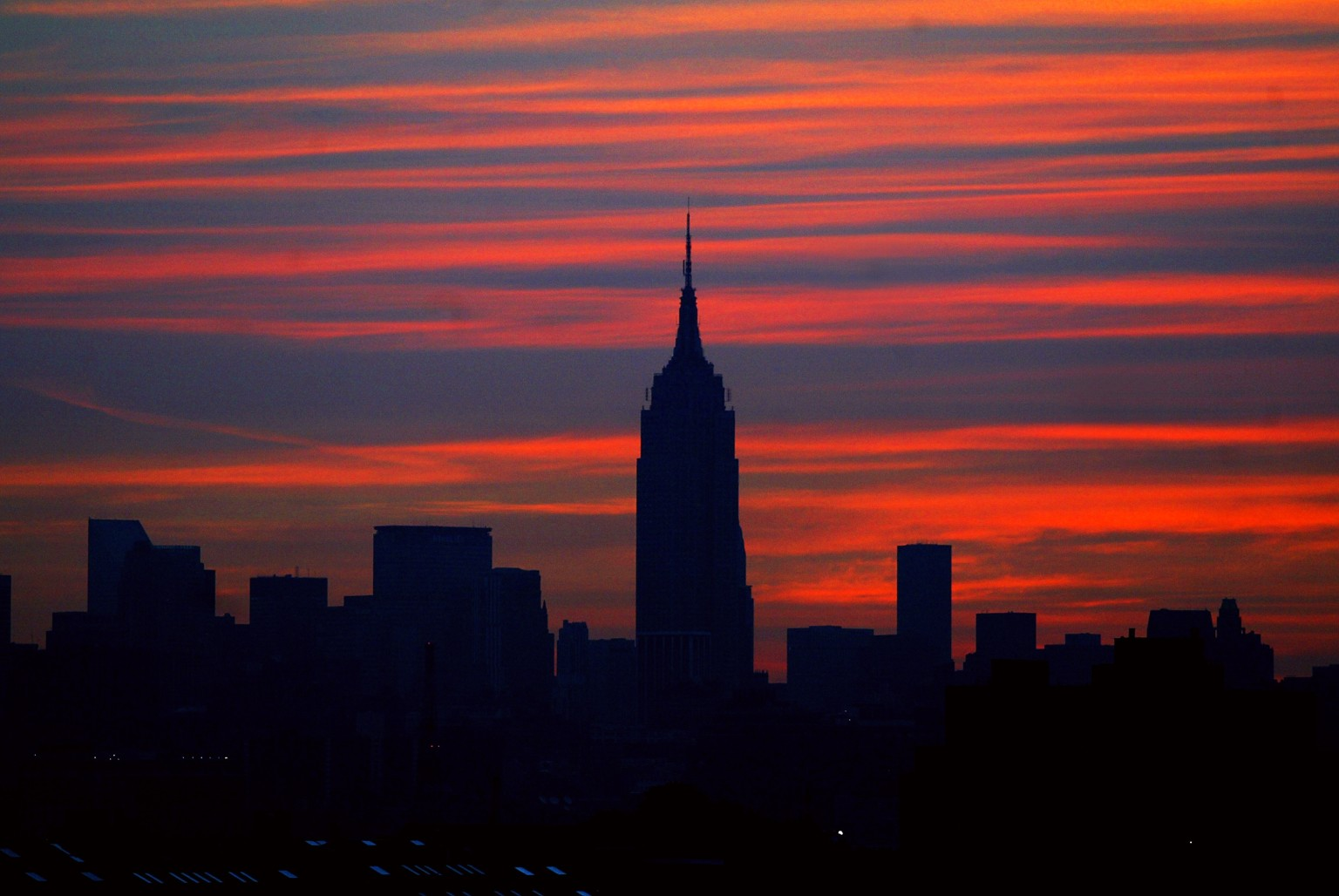 Manhattan skyline is dark as the sun comes up on the morning